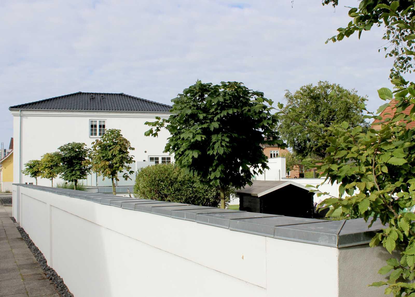 Havemuren her er lavet så den matcher godt med husets stil, og komplementerer til et flot helhedsindtryk af villaen.