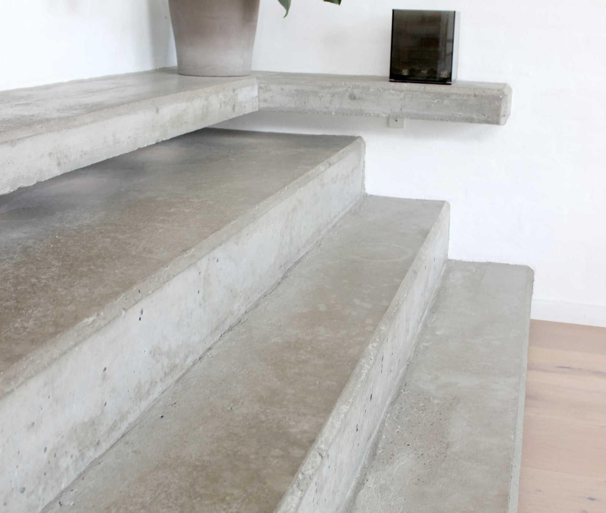 Betontrappen fungerer både som møbel og bindeled mellem det oprindelige hus og tilbygning. Trappen skaber kontrast og tilføjer en flot stoflighed i rummet.